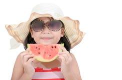 逗人喜爱的女孩佩带的泳装吃被隔绝的西瓜 库存照片