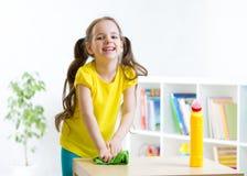 逗人喜爱的女孩做清洁在儿童居室在 免版税图库摄影