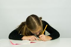 逗人喜爱的女孩做着她的家庭作业 免版税库存图片
