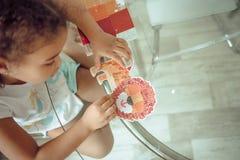 逗人喜爱的女孩做补花,胶合五颜六色的房子,应用颜色纸使用胶浆棍子,当做艺术和工艺时 免版税库存图片