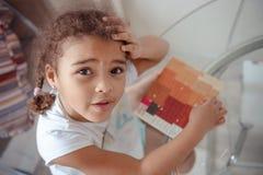 逗人喜爱的女孩做补花,胶合五颜六色的房子,应用颜色纸使用胶浆棍子,当做艺术和工艺时 免版税图库摄影