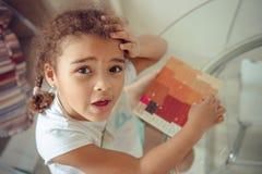 逗人喜爱的女孩做补花,胶合五颜六色的房子,应用颜色纸使用胶浆棍子,当做艺术和工艺时 图库摄影