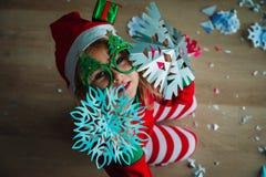 逗人喜爱的女孩切开了圣诞节庆祝的雪花 库存照片