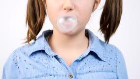 逗人喜爱的女孩口香糖和吹bubblegum泡影轻快优雅画象的慢动作关闭  股票视频