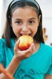 逗人喜爱的女孩吃一个苹果 免版税库存照片