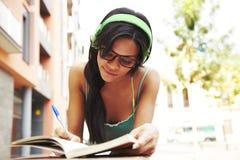 逗人喜爱的女孩听的音乐学习 免版税库存图片
