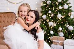 逗人喜爱的女孩和他的母亲坐在deco的白色礼服的 免版税库存照片