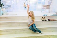 逗人喜爱的女孩和使用坐楼梯的便服的 免版税库存图片