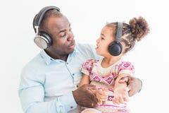 逗人喜爱的女孩和她的爸爸听到与耳机的音乐在白色背景 免版税库存图片