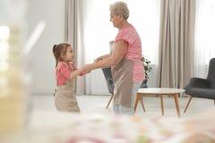 逗人喜爱的女孩和她的祖母跳舞 免版税图库摄影