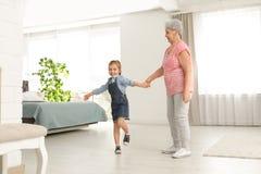 逗人喜爱的女孩和她的祖母跳舞 免版税库存照片