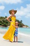 逗人喜爱的女孩和美丽的母亲海滩的 免版税库存照片