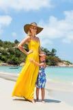 逗人喜爱的女孩和美丽的母亲海滩的 免版税库存图片