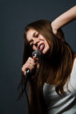 逗人喜爱的女孩唱歌年轻人 免版税库存照片