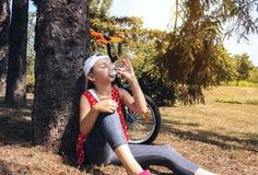 逗人喜爱的女孩喝从塑料瓶的水 免版税库存图片