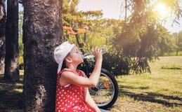 逗人喜爱的女孩喝从塑料瓶的水 库存照片