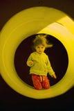 逗人喜爱的女孩在儿童` s操场喜欢使用在隧道 库存图片