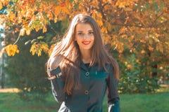 年轻逗人喜爱的女孩在公园站立在一个晴天并且微笑 库存图片