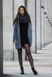 逗人喜爱的女孩在大厦背景站立  免版税库存图片