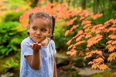 逗人喜爱的女孩在庭院里 免版税库存图片