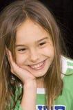 逗人喜爱的女孩在手中微笑的和休息的题头 免版税库存照片
