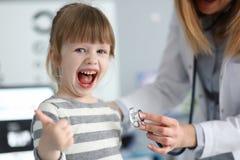 逗人喜爱的女孩在显示尊敬谢意的医生办公室和为与赞许的优质的服务批准 库存图片