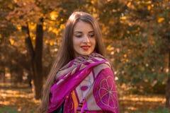 逗人喜爱的女孩在有一条大桃红色围巾的公园站立在肩膀并且看  免版税图库摄影