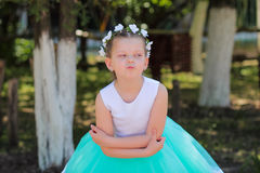 逗人喜爱的女孩在有在她的头的,挥动和拥抱的人造花花圈的蓝色和白色礼服穿戴了, 免版税库存图片