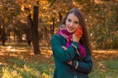 逗人喜爱的女孩在有花揪小树枝的秋天公园在她的手上站立  免版税库存图片
