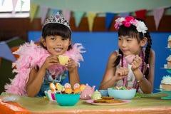 逗人喜爱的女孩在桌上在生日聚会期间 免版税库存照片