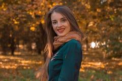 逗人喜爱的女孩在秋天公园站立并且微笑 库存图片