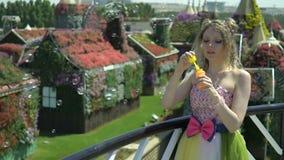 逗人喜爱的女孩在花园里吹在阳台的泡影 童话样式 做肥皂泡的俏丽的妇女 影视素材