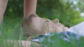 逗人喜爱的女孩在草的男孩的亲吻的前额和鼻子特写镜头画象  两三愉快 股票视频