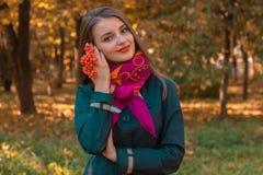 逗人喜爱的女孩在Scharfe在公园在她的手上站立并且拿着花揪小树枝  免版税库存照片