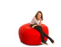 年轻逗人喜爱的女孩坐圆形红色装豆子小布袋椅子 图库摄影