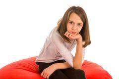 逗人喜爱的女孩坐圆形红色装豆子小布袋椅子 库存图片
