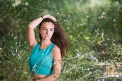 逗人喜爱的女孩坐在绿草中的台阶 免版税库存图片