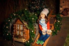 逗人喜爱的女孩坐屋顶并且等待圣诞老人 圣诞节装饰装饰新家庭想法 免版税库存图片