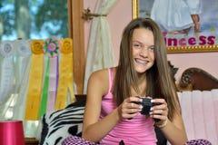 逗人喜爱的女孩坐床-电子游戏 库存照片