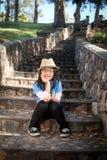 逗人喜爱的女孩坐的台阶 免版税库存图片