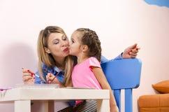 逗人喜爱的女孩她亲吻的小母亲 免版税库存照片
