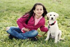 逗人喜爱的女孩小狗步行公园绿草开会 免版税库存照片