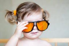 逗人喜爱的女孩小的橙色太阳镜 免版税库存图片
