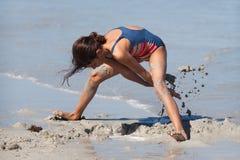 逗人喜爱的女孩开掘在沙子的一个漏洞 库存图片