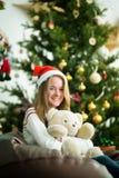 逗人喜爱的女孩拥抱在圣诞前夕的玩具熊 免版税库存图片