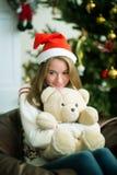 逗人喜爱的女孩拥抱在圣诞前夕的玩具熊 免版税图库摄影