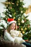逗人喜爱的女孩拥抱在圣诞前夕的玩具熊 免版税库存照片