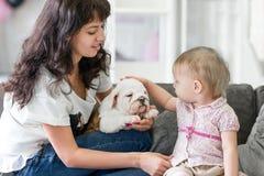 逗人喜爱的女孩接触在她的母亲的手上的小狗 库存照片