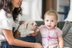 逗人喜爱的女孩接触在她的母亲的手上的小狗 免版税库存图片