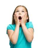 逗人喜爱的女孩握她的在惊讶的面孔 免版税库存照片